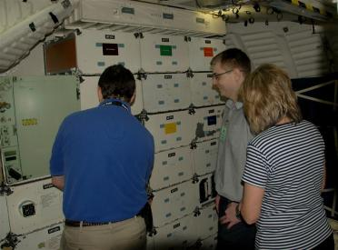 Matt shows Mark and Marianne some of the middeck locker space