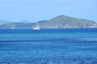 Sailboat in the blue waters of Mahoe Bay