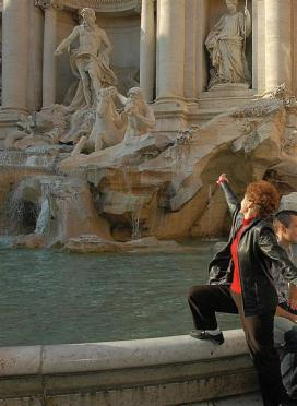 Geri tosses a coin into the Trevi Fountain
